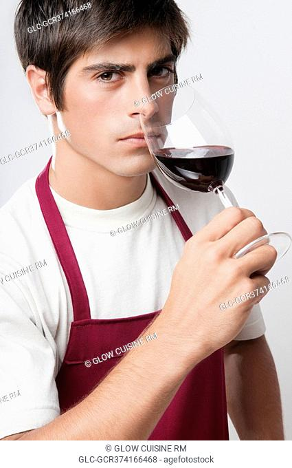 Close-up of a man smelling a glass of red wine