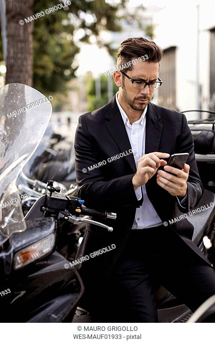 Businessman at motor scooter in the city using cell phone