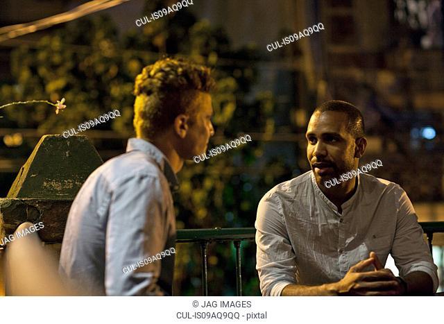 Two men sitting at table at bar, talking