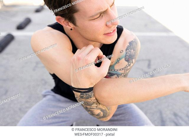 Tattooed young man doing stretching exercises