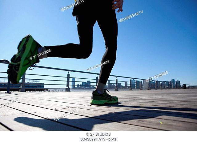 View of an athlete's legs running across walkway