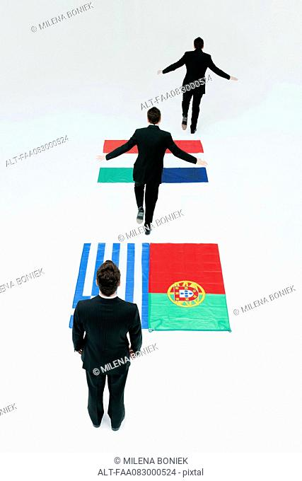 Businessman running across Greek, Portuguese, Italian and French flags