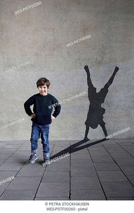 Germany, Duesseldorf, portrait of smiling little boy and shadow of Duesseldorf's cartwheeler on wall
