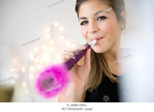Young woman blowing noisemaker at party