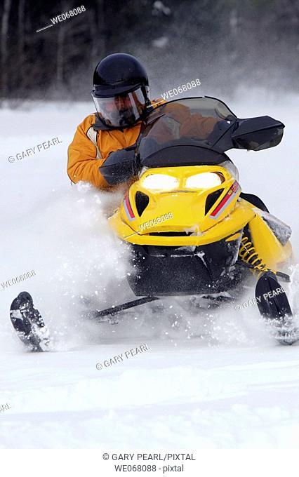 Man snowmobiling through deep snow