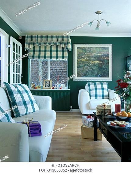 Green checked cushions on white sofa and armchair in dark green living room with green checked blind and wooden floor