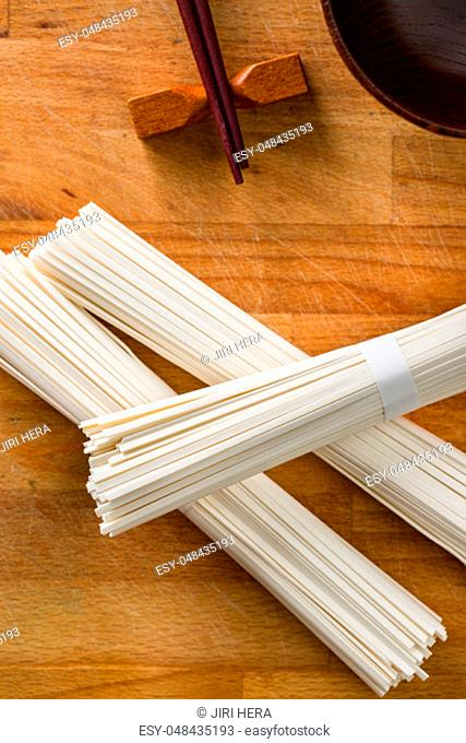 Raw udon noodles on wooden table. Top view