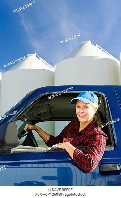 farmgirl in truck next to grain bins in a farmyard, near Lorette, Manitoba