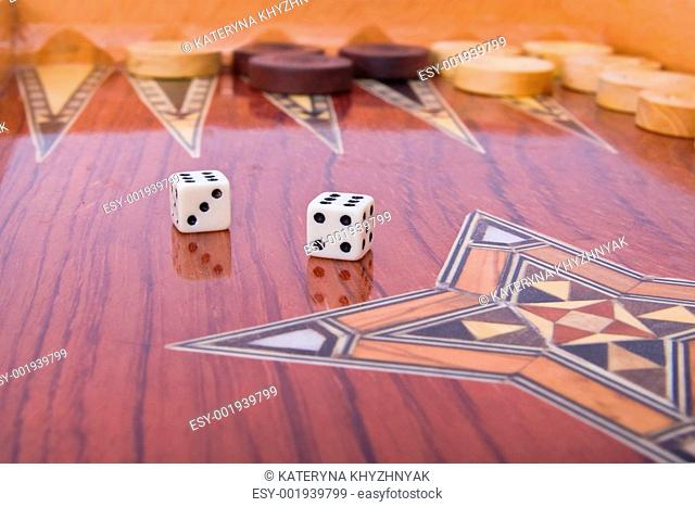 Two dices with reflection on wooden handmade backgammon board is