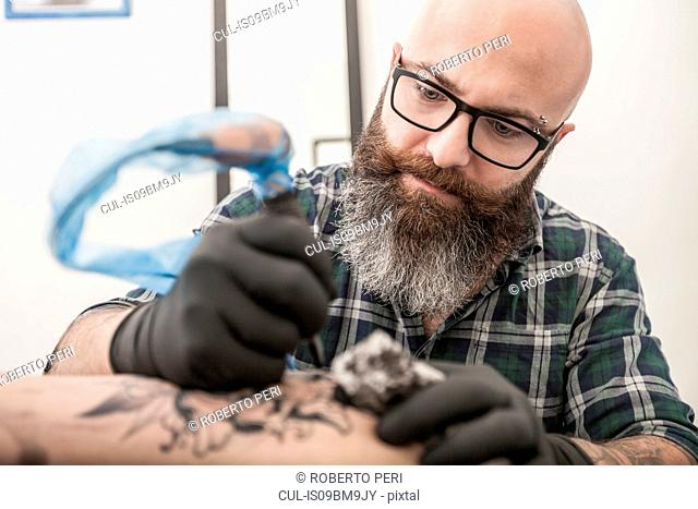 Tattooist drawing on arm of client