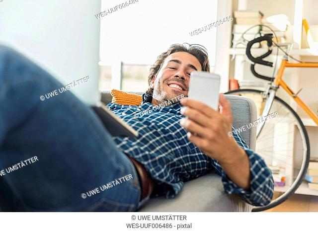 Young man lying on the couch with laptop looking at his smartphone