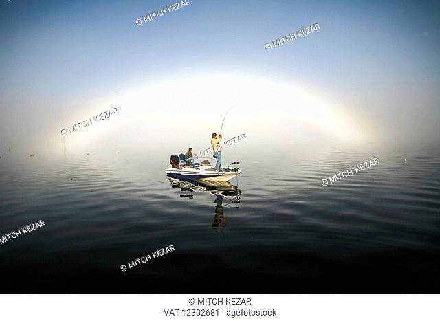 Fisherman In Boat On Water