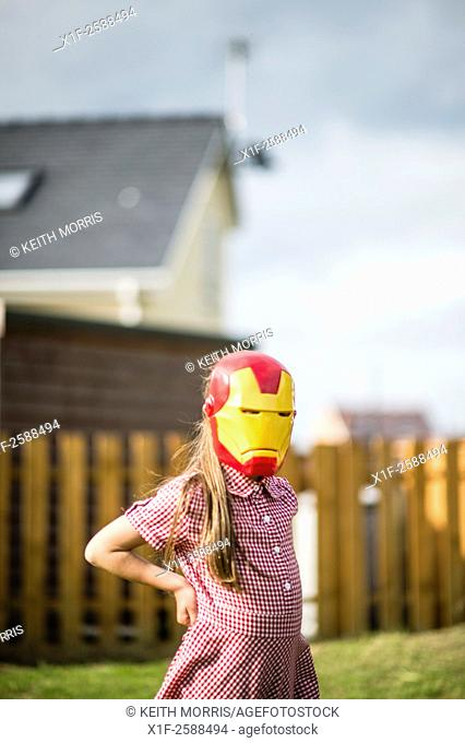 Childhood Games - young girl wearing an IronMan mask : Pre-teen primary school age children playing outdoors on a summer evening