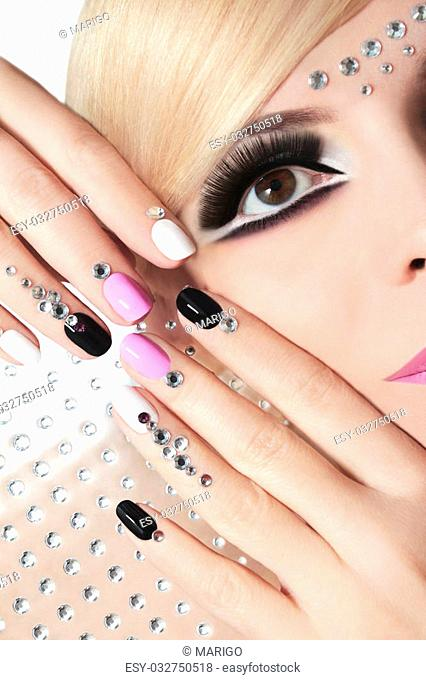 Fashion nails and makeup with rhinestones on nails and on the face of a woman with blond hair