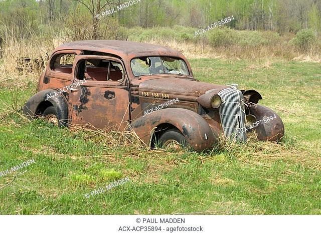 Rusty old car sitting in a field in Ramara Township, Ontario, Canada