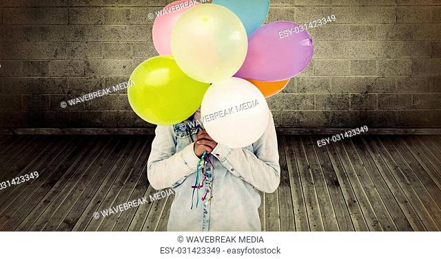Composite image of woman hiding her face with bunch of colorful balloons