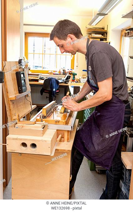Instrument maker fixing reeds of accordion, tuning,