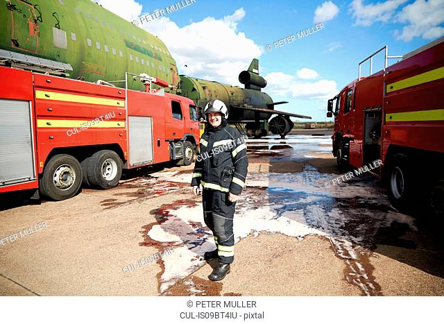 Fire training, fireman by fire engines at training facility, portrait