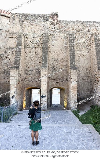 Girl in front of ancient city walls. Alghero, Sardinia. Italy