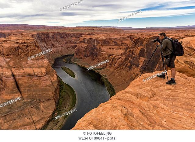 USA, Arizona, Page, Colorado River, Glen Canyon National Recreation Area, man taking picture at Horseshoe Bend