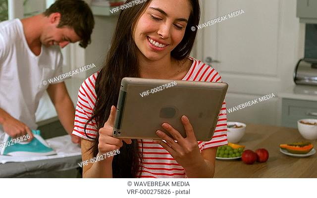 Handsome man ironing while woman is using tablet