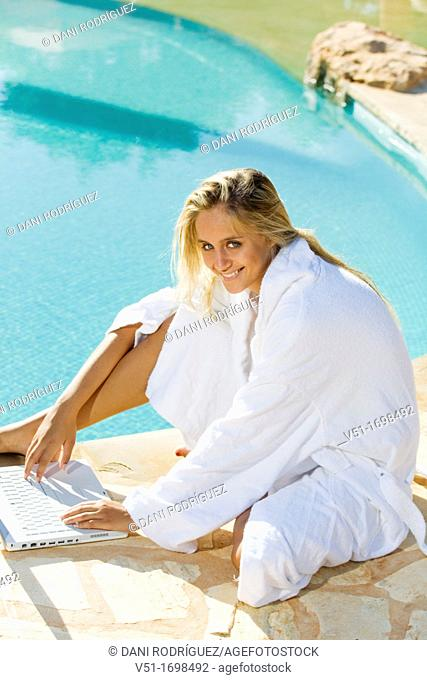 Young blonde woman at pool using laptop and smiling at camera