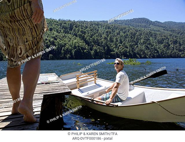 Low angle view of woman approaching mature man in rowboat