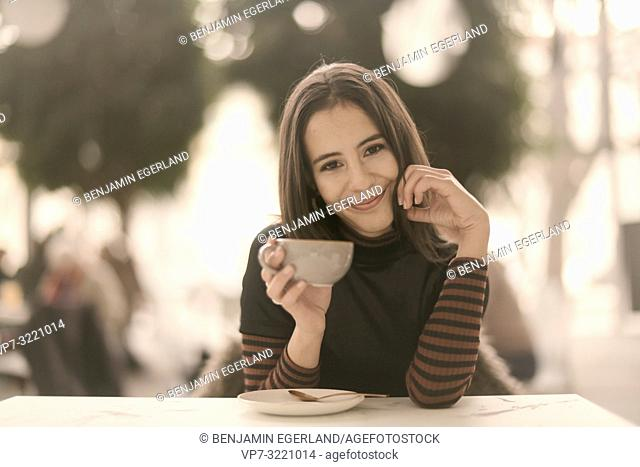 portrait of pleased woman holding coffee cup while enjoying break at table in café, in Munich, Germany