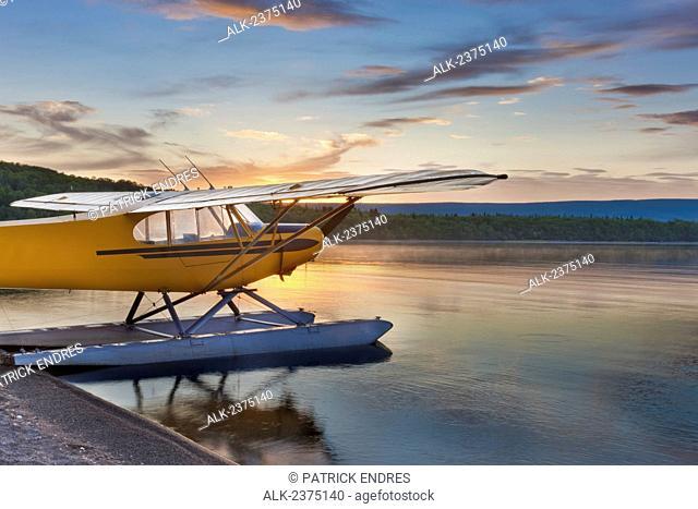 Morning sunrise over Naknek lake with a Super Cub bush plane on floats along the shore, Katmai National Park, southwest Alaska