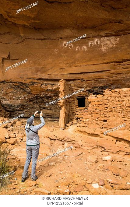 Hiker taking a photograph, Ancestral Pueblo, up to 1,000 years old, Bears Ears National Monument; Utah, United States of America