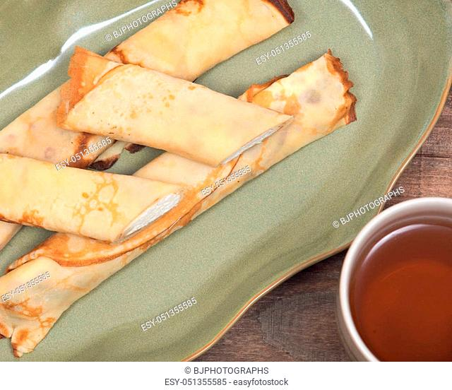 Delicious cheese blintz on green plate and cup of tea on wooden vintage tray