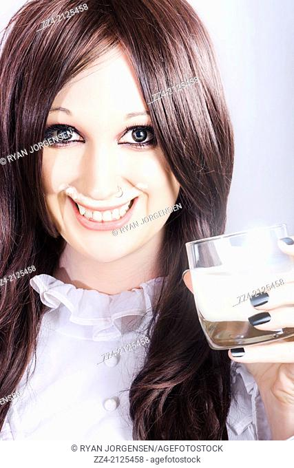 Lifestyle portrait of a cute smiling woman drinking glass of fresh full cream milk with a milky moustache