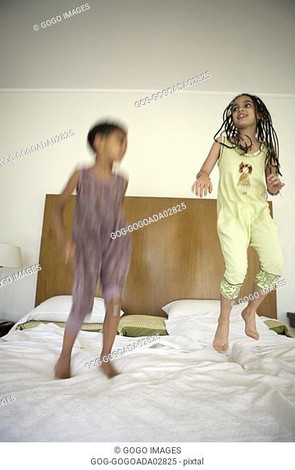 Siblings jumping on bed