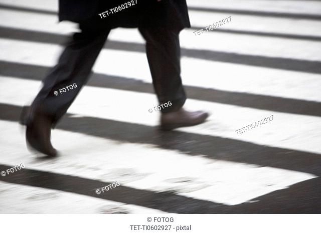 USA, New York state, New York city, low section of men crossing zebra crossing