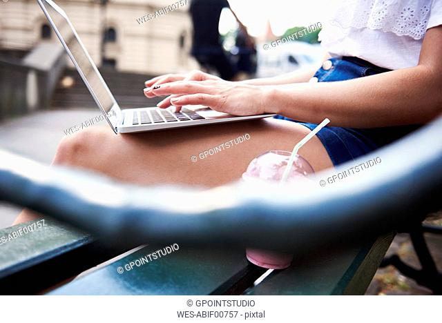 Young woman sitting on bench using laptop, partial view