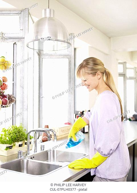 Woman in kitchen at sink cleaning