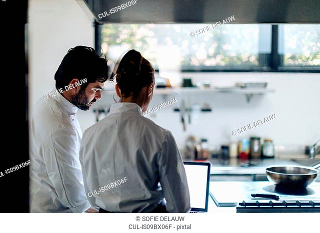 Chefs having discussion over laptop in kitchen