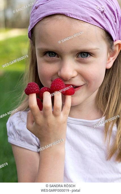 Germany, Bavaria, Girl holding raspberries on her finger