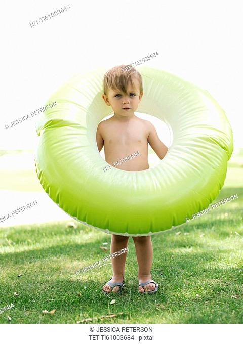 Boy (2-3) standing with inflatable ring