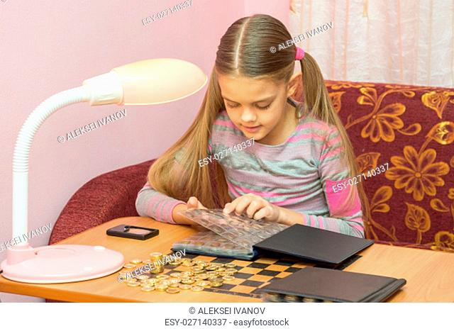 Girl at the table leafing through the album with coins