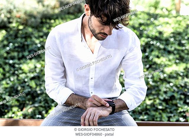 Young man sitting outdoors using smartwatch