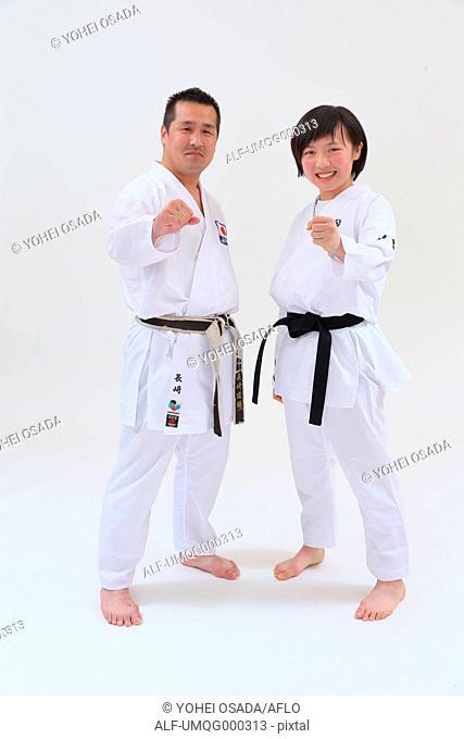 Japanese kid in karate uniform training with teacher on white background