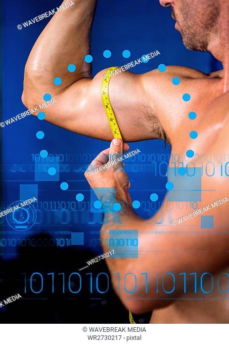 Fit man measuring biceps with measuring tape