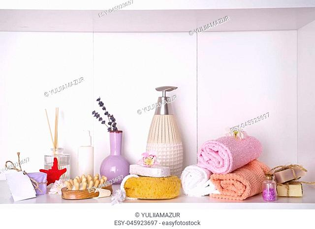 Spa and wellness setting with soaps, candle, aroma chopsticks and towels on a shelf , copy space . Dayspa nature products