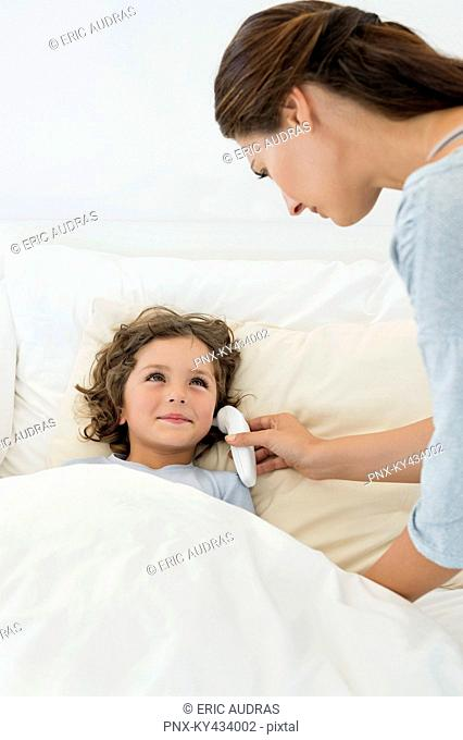Woman checking fever of her son with a thermometer