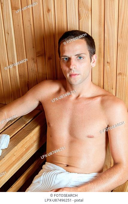 Serious man resting in the sauna