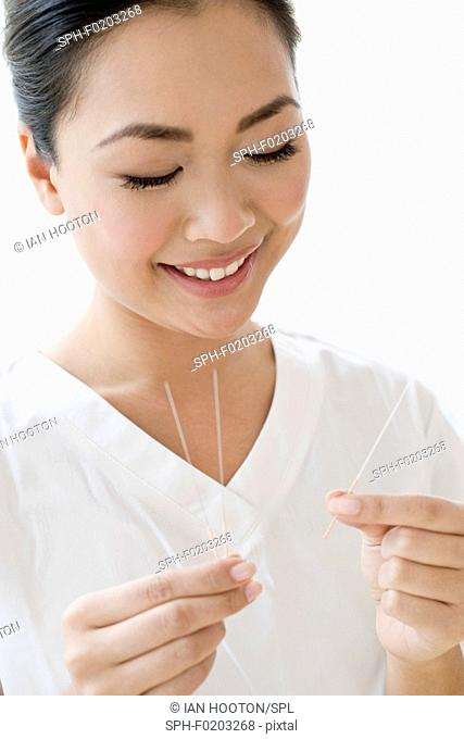 Woman holding acupuncture needles