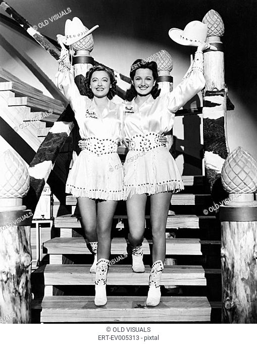 Two young women stepping down a staircase waving their western hats All persons depicted are not longer living and no estate exists Supplier warranties that...