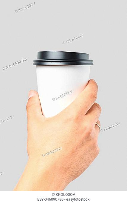 Mockup of men's hand holding white paper large size cup with black cover isolated on grey background