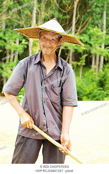 Farmer holding a rake in a field, Zhigou, Shandong Province, China